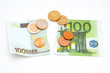 Torn Euro banknote and coins on white background