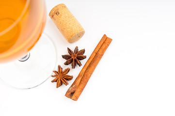 Wine glass, cork and cinnamon on white background