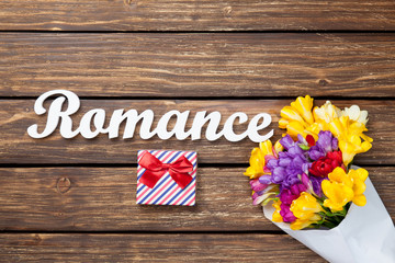 Gift box and bouquet of flowers with word Romance