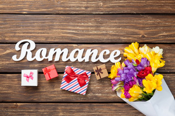 Gift boxes and bouquet of flowers with word Romance