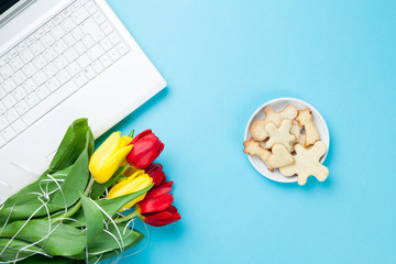 White computer and bouquet of tulips with cookies
