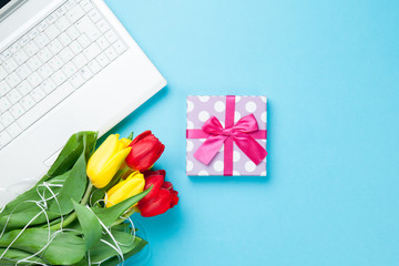 White computer and bouquet of tulips with gift