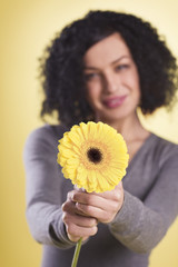 Cheerful woman holding a yellow flower.