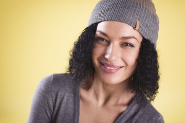 Close up of a cheerful trendy girl on yellow background.
