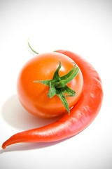 chili peppers and tomato next to each other on a white backgroun