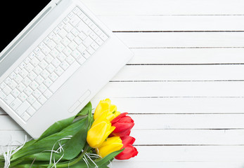 White computer and bouquet of tulips