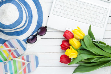 White computer and flip flops shoes with tulips