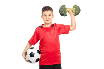 Little kid holding a football and broccoli dumbbell
