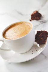 Angled view of cappuccino or latte coffee with chocolate brownie