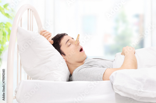 Man sleeping with a clothespin on his nose - 79890360