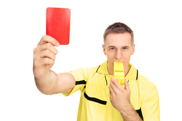 Referee showing red card and blowing huge whistle
