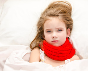 Little girl lying in the bed with thermometer