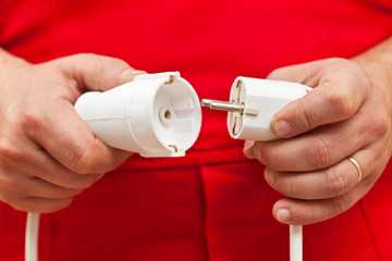 Male hands plugging or unplugging electrical wires