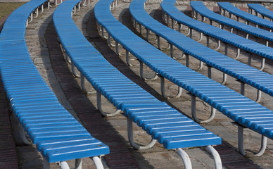Row of blue wooden seats on a spectator grandstand photo.