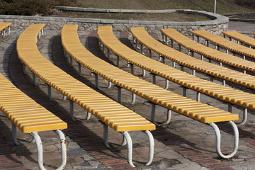 Row of yellow wooden seats on a spectator grandstand photo