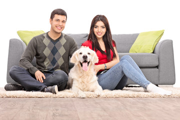 Young couple sitting on the floor with a dog