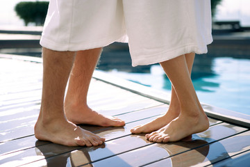 Legs of a couple in bathrobe at a poolsid