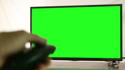 Male hand with TV remote switching channels on green screen