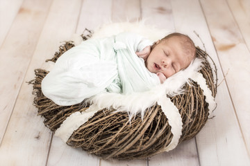Newborn Baby liegt in einem Holzkranz