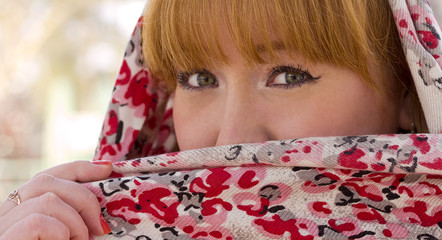 The red-haired girl closes half of his face with a scarf.