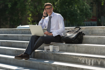 Man with laptop calling by phone