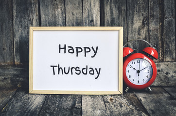 Happy Thursday message on white board and red retro clock  by wo