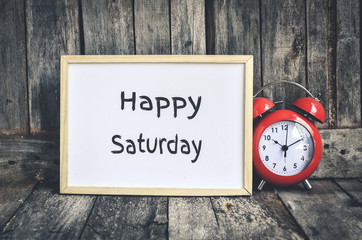 Happy Saturday message on white board and red retro clock  by wo