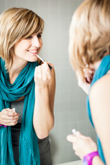 Pretty, young woman applying mascara /eyeshadows in front of a m