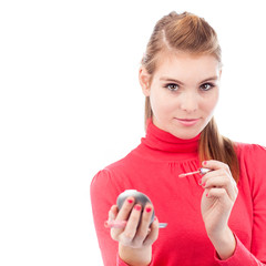 pretty young woman applying lip gloss (on white background)