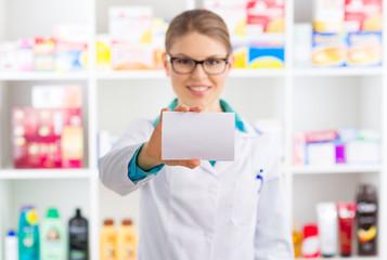 Smiling pharmacist showing blank paper over shelves background