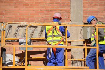trabajadores encima de un andamio