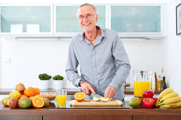 Mature man in the kitchen prepare fruits for breakfast.