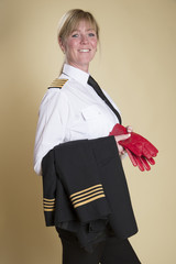 Airline Captain standing in uniform holding red gloves