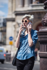Young blonde woman portrait talking at the phone in front of Ope