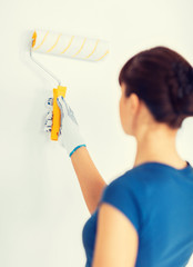 woman with roller and paint colouring the wall