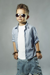 fashionable little boy in sunglasses.stylish kid in jeans