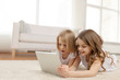 two little girls with tablet pc at home