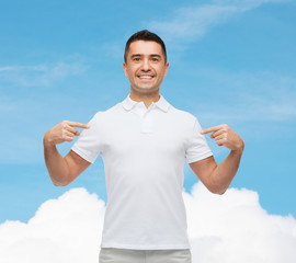 smiling man in t-shirt pointing fingers on himself
