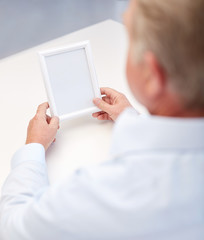 close up of old man holding blank photo frame