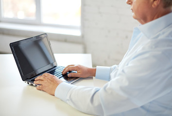 close up of senior man with laptop typing