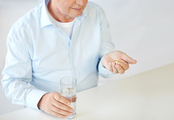 close up of old man with pills and water glass