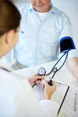 close up of doctor measuring blood pressure