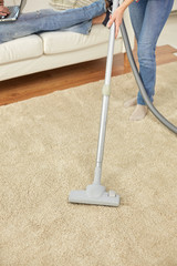 close up of couple legs and vacuum cleaner at home