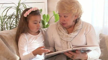 Grandmother reading a book with her granddaughter