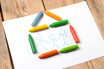 Oil pastel crayons lying on a paper with painted family