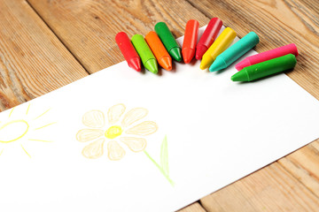 Oil pastel crayons lying on a paper with painted flower and sun
