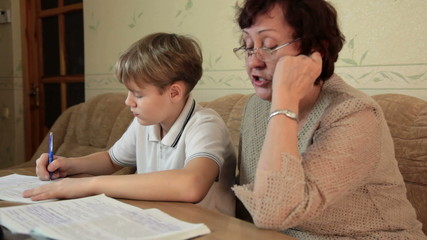 Grandma helping her grandson doing homework