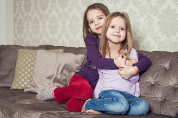 Portrait of two cute sisters at home. Family