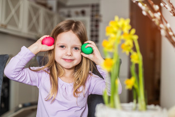 Beautiful little girl with easter eggs. Cozy home atmosphere