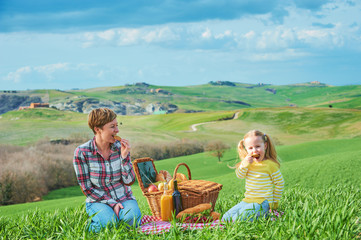 Mother and daughter arranged picnic on the green spring grass in